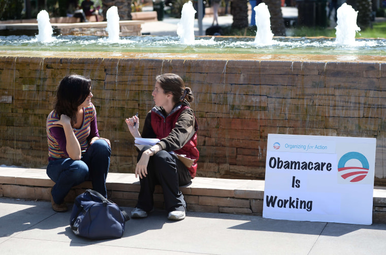 An Affordable Healthcare Act supporter (R) talks with a student (L) about the law on the campus of Santa Monica City College in Santa Monica, California, October 10, 2013.