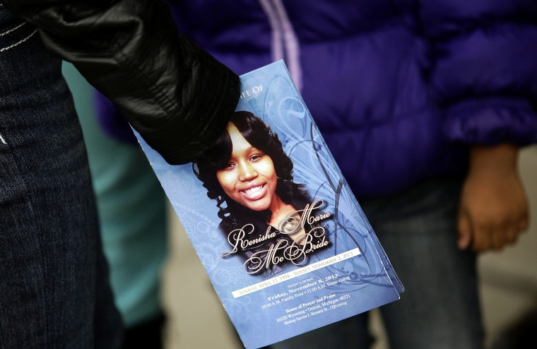 A mourner holds an obituary displaying a picture of shooting victim Renisha McBride during her funeral service in Detroit