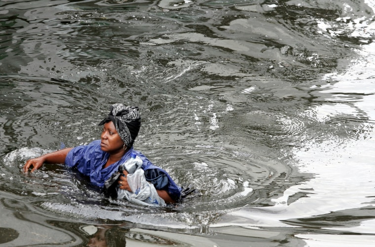 A woman walks through chest-deep floodwater from actual Hurricane Katrina in New Orleans, August 30, 2005.