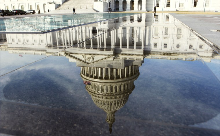 The dome of the Capitol is reflected in a puddle in Washington, Feb. 17, 2012.