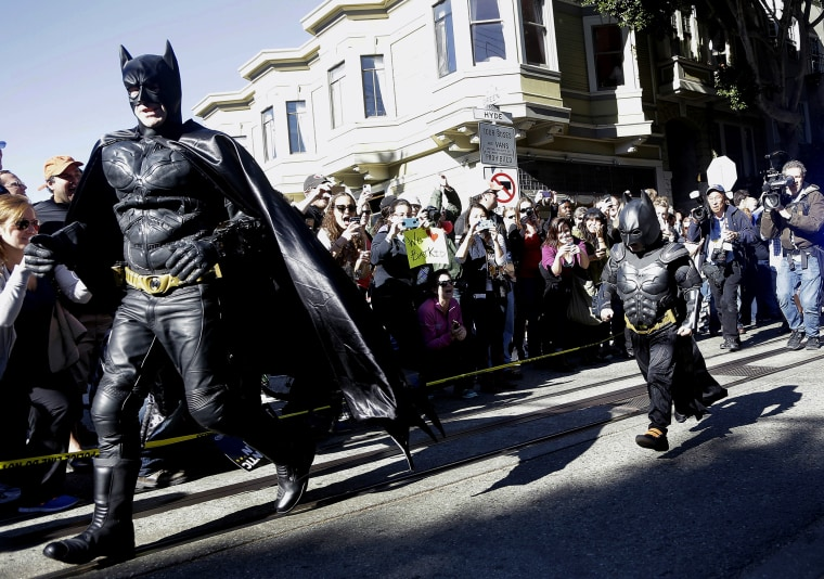 Miles Scott, dressed as Batkid, right, runs with Batman after saving a damsel in distress in San Francisco, Nov. 15, 2013.
