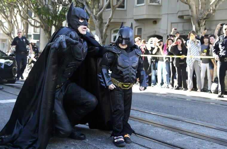 Miles Scott, dressed as Batkid, right, walks with Batman before saving a damsel in distress in San Francisco on Nov. 15, 2013.