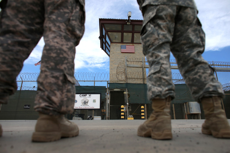 Military officers stand at the entrance to Camp VI and V at the U.S. military prison for 'enemy combatants' on June 25, 2013 in Guantanamo Bay, Cuba.