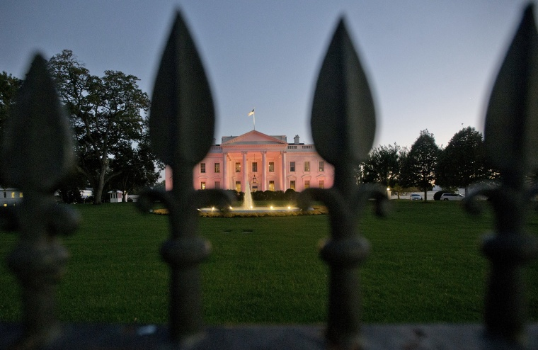 The White House in Washington is bathed in pink light on Oct. 24, 2013.