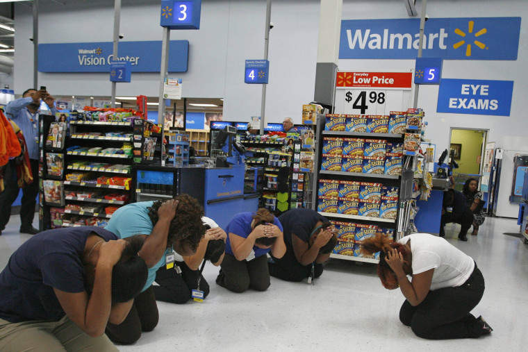 """Walmart employees practice the drop, cover, and hold on technique during the \""""Great ShakeOut\"""" \"""" earthquake drill at Walmart in Torrance, California October 17, 2013."""