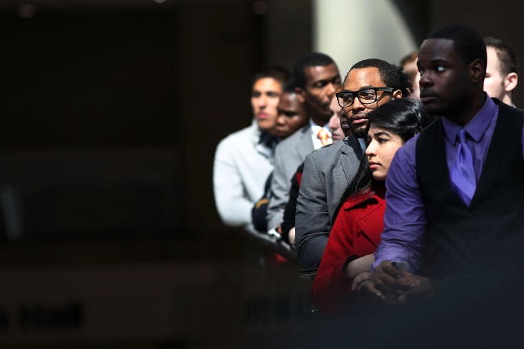 Job seekers wait in line to meet with employers at a job fair in NYC, April 26, 2013.