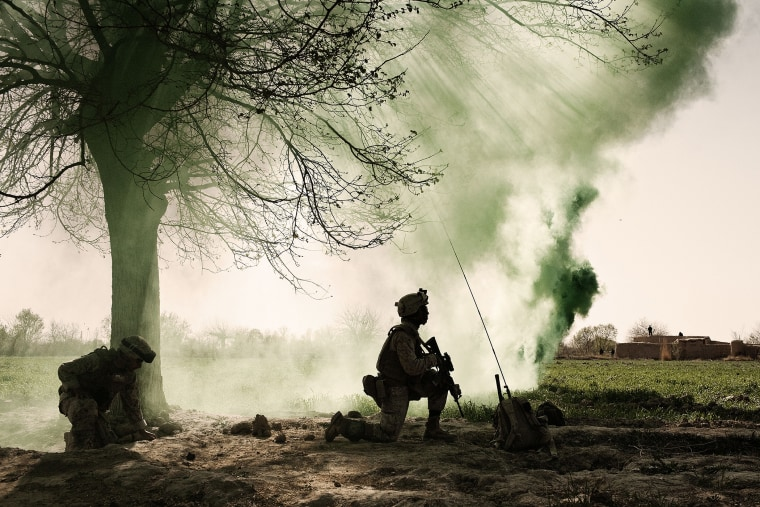 US Marines kneel behind a smoke screen at a helicopter landing zone in Marja, Afghanistan, March 2010.