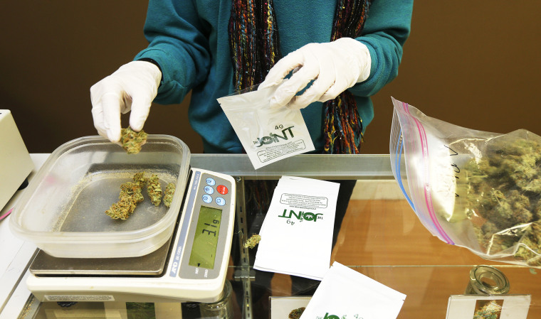 Monique Rydberg weighs and packages medical marijuana in Seattle, Oct. 16, 2013.