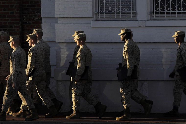 Military personnel walk by the Washington Navy Yard on Sept 17, 2013 in Washington, DC.