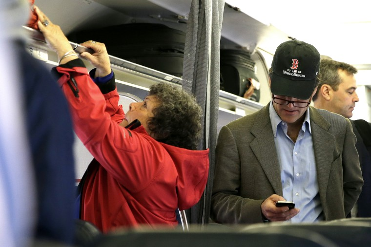 In this  Oct. 31, 2013 file photo, a passenger checks his cell phone while boarding a flight, in Boston.