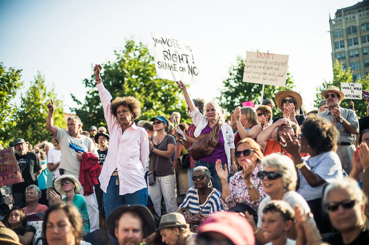 A crowd cheer in support during a speech by Rev Dr. William Barber II, president of the North Carolina NAACP in Asheville, NC's Pack Square Park during Mountain Moral Monday on Aug 5, 2013.