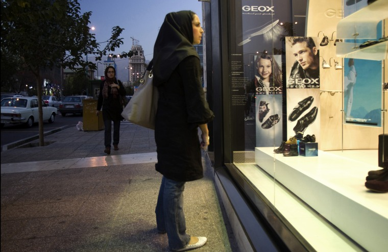 An Iranian woman looks in the window of a Geox store in northern Tehran