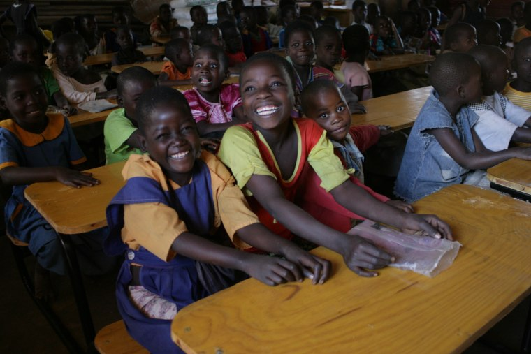 Kids sitting at their new desks, brought to them through the K.I.N.D. program.
