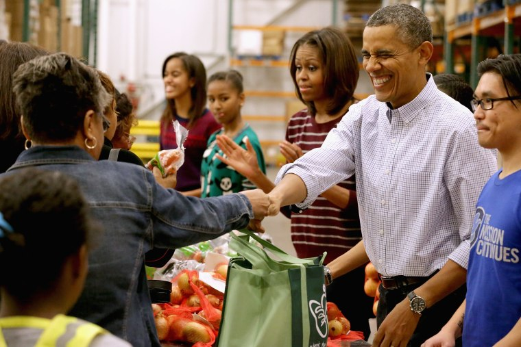 President Barack Obama, first lady Michelle Obama, and their daughters Sasha Obama, 12, and Malia Obama, 15, help pack and distribute bags of food to needy children and seniors at the Capital Area Food Bank November 27, 2013 in Washington, DC.