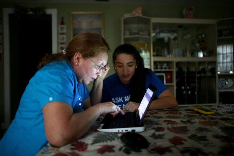 Janelle Arevalo (R), an insurance agent with Sunshine Life and Health Advisors, makes a house call to sign up Sandra Berrios for an insurance plan under the Affordable Care Act on Nov. 14, 2013 in Miami, Fla.