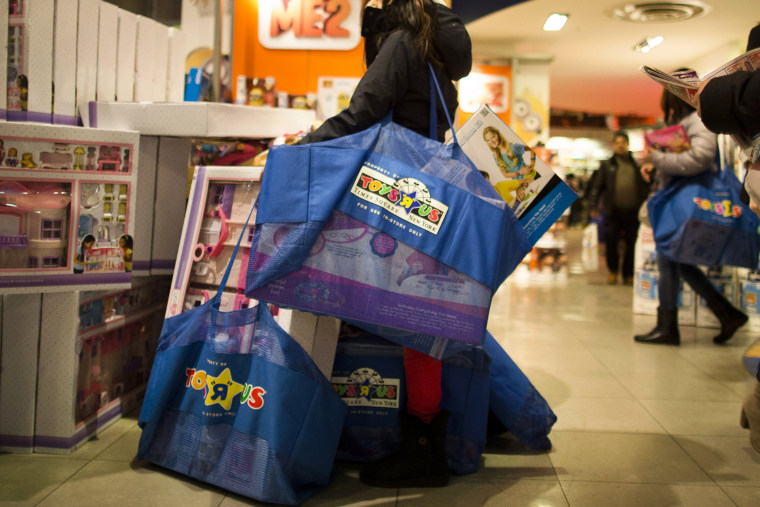 A shopper waits with her bags in the Times Square Toys R' Us on Nov. 28, 2013, Thanksgiving Day, in New York.