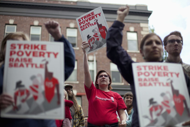 Joelle Craft (C) holds a sign during a rally and strike aimed at the fast-food industry and the minimum wage in Seattle, Washington August 29, 2013.