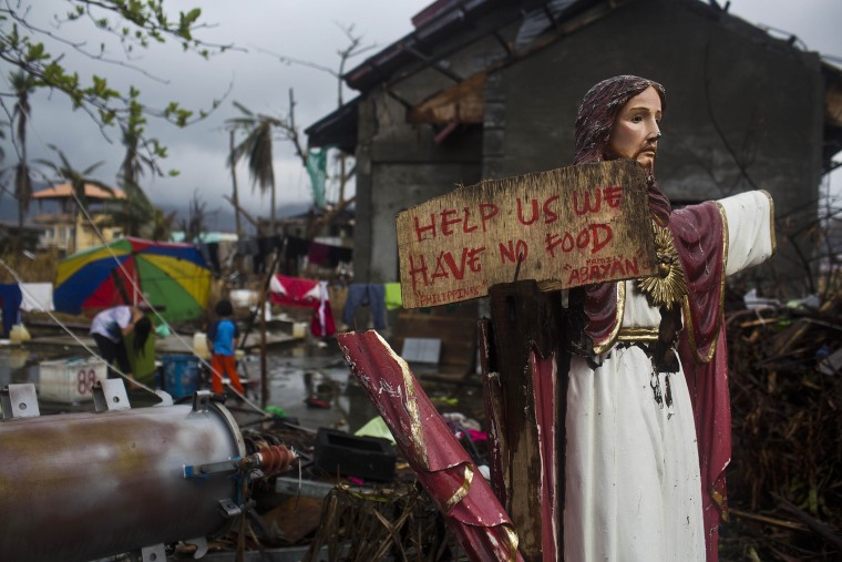 A plea for help painted on a sign hangs from a damaged statue of Jesus in a Typhoon Haiyan destroyed neighborhood in Tacloban, Philippines on Nov. 22, 2013.