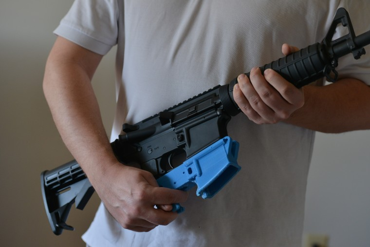 A man holds an AR-15 assault rifle with a lower receiver made of ABS (Acrylonitrile Butadiene Styrene) plastic constructed by a 3D printer, Feb. 12, 2012.