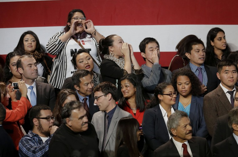 A group yells immigration reform chants at President Barack Obama as he leaves after speaking about immigration reform, Monday, Nov 25, 2103, at the Betty Ann Ong Chinese Recreation Center in San Francisco.
