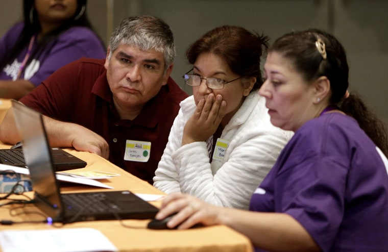 Carlos Barajas, left, and his wife, Martha, center, look over their health insurance plan options with volunteer Elizabeth Lira, at a health fair in Sacramento, Calif on Nov. 9, 2013.