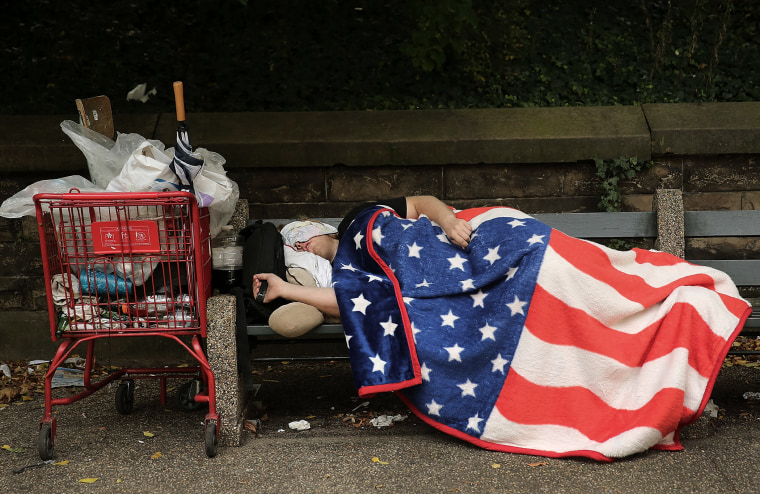A homeless man sleeps under an American Flag blanket on a park bench on Sept. 10, 2013 in the Brooklyn borough of New York City.