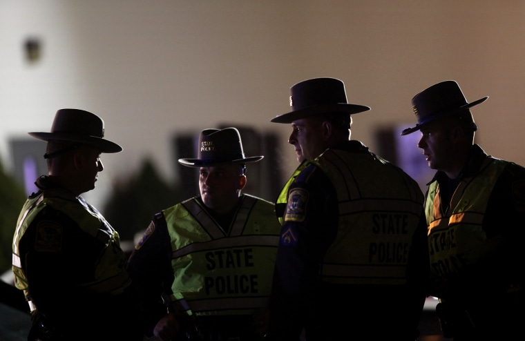 A Connecticut State Police Officers stand outside the Sandy Hook Volunteer Fire and Rescue Company near Sandy Hook Elementary School in Newtown, Connecticut Dec. 14, 2012.