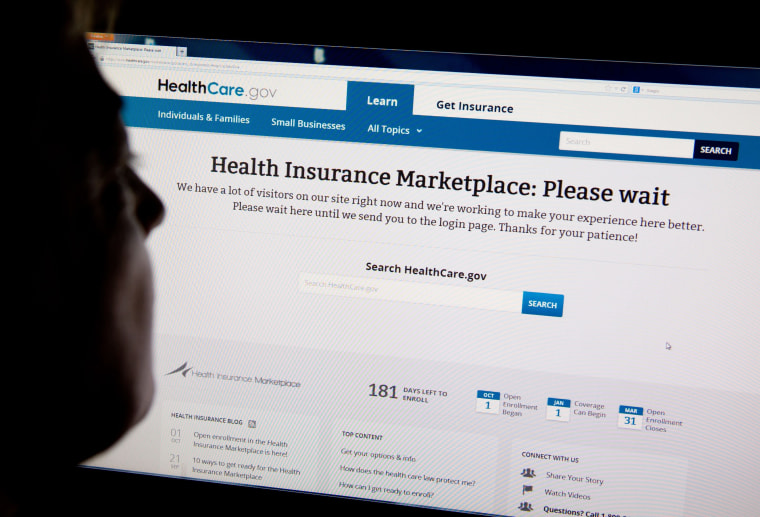 """A woman looks at the HealthCare.gov insurance exchange internet site showing a """"Please wait"""" page, in this October 1, 2013 file photo in Washington, DC."""