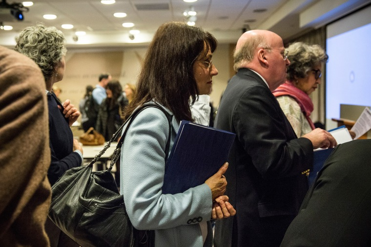 A woman prepares to speak to potential employers at a jobs fair in New York, Nov. 20, 2013.