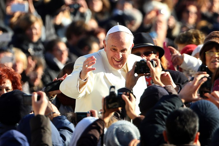 Pope Francis waves to the faithful as he arrives for his weekly audience in Vatican City, Dec. 4, 2013.