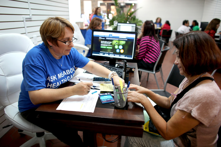 Mercy Cabrera (L), an insurance agent with Sunshine Life and Health Advisors, helps Amparo Gonzalez  purchase an insurance policy under the Affordable Care Act at the store setup in the Westland Mall on Nov. 14, 2013 in Hialeah, Fla.