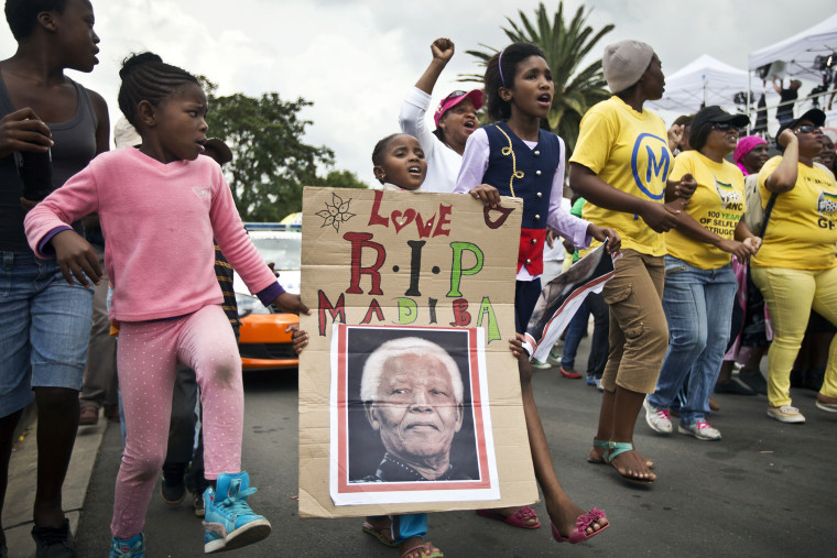 A young girl marches with others to celebrate Nelson Mandela's life, in the street outside his old house in Soweto, Johannesburg, South Africa, Dec. 6, 2013.