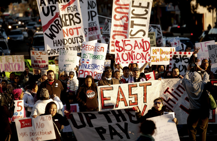 Demonstrators demanding an increase in worker wages march to a Jack in The Box fast food outlet in Oakland, California Dec. 5, 2013.