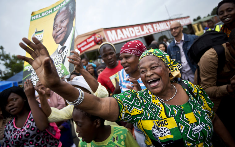Mourners sing and dance to celebrate the life of Nelson Mandela, in the street outside his old house in Soweto, Johannesburg, South Africa on Dec. 6, 2013.