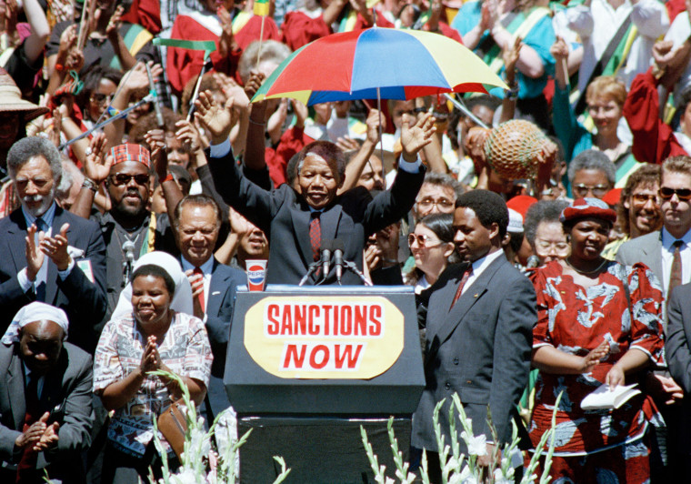 Nelson Mandela, deputy president of the African National Congress, gestures to a capacity crowd at the Oakland Coliseum on June 30, 1990, during the last stop of his eight city U.S. tour.