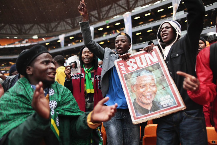 Supporters of late South African president Nelson Mandela sing and dance in the rain as they arrive to attend the memorial service in Johannesburg, Dec. 10, 2013.