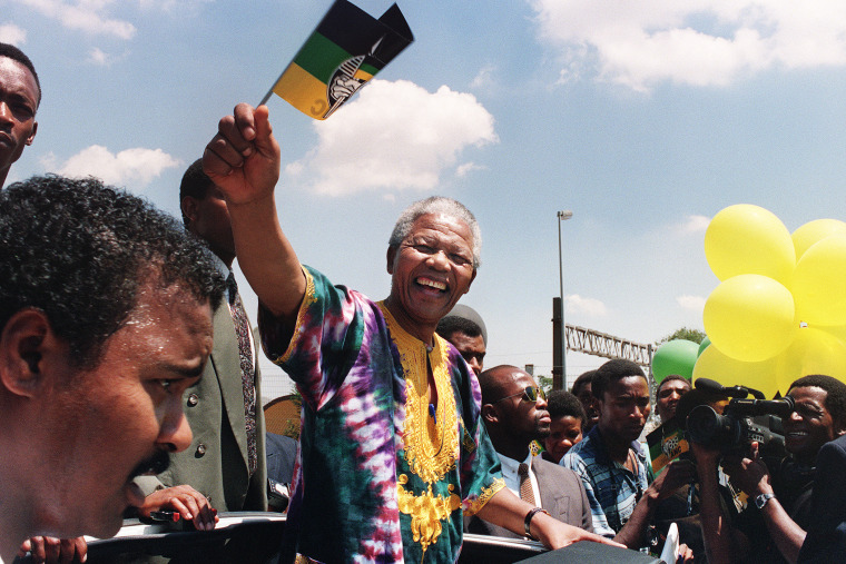 Nelson Mandela waves to supporters while campaigning for the presidential election, Jan. 29, 1994.