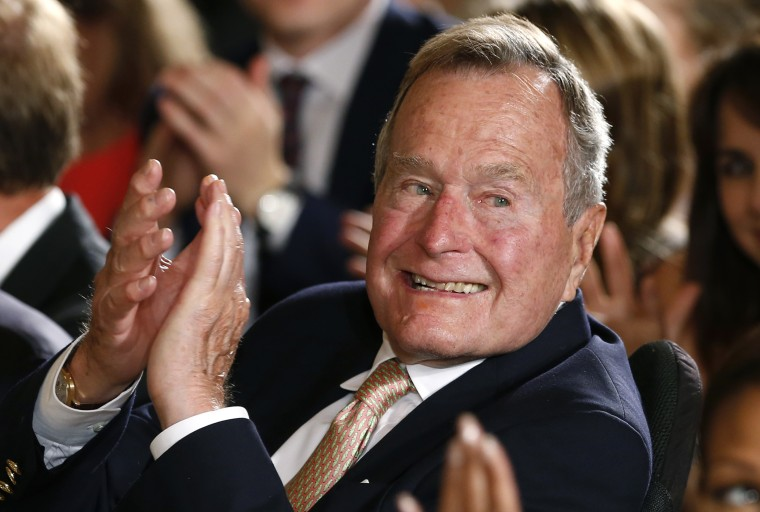 Former President George H. W. Bush applauds during an event at the White House on July 15, 2013.