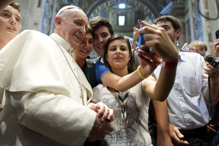 Pope Francis poses with youths during a meeting with the Piacenza diocese in Saint Peter's Basilica, AUg. 28, 2013.