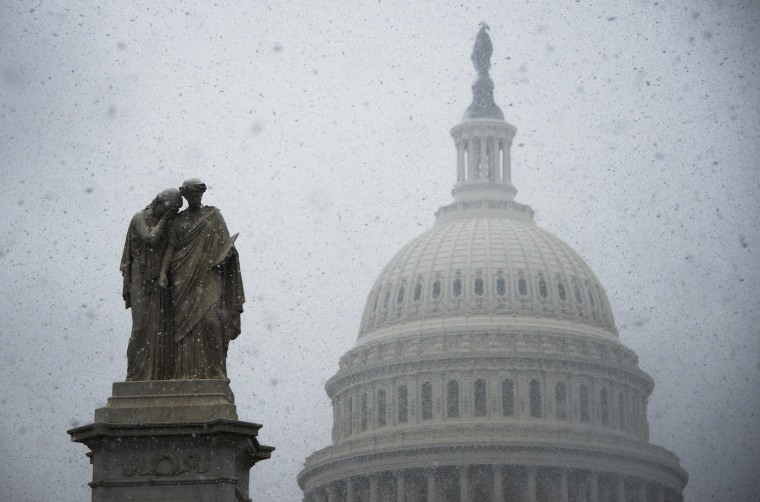 Snow begins to gather on a statue outside the US Capitol Building in Washington, DC, Dec.10, 2013.