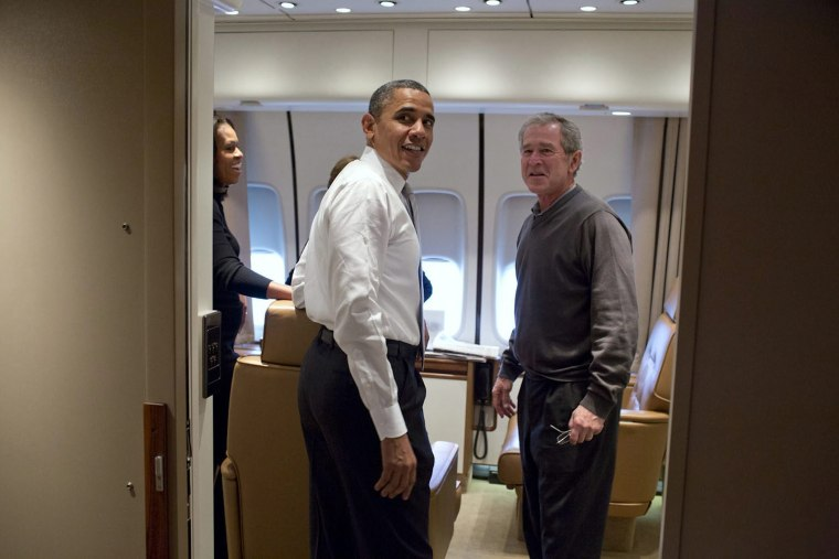 Barack Obama jokes with George W. Bush shortly after boarding Air Force One en route to Nelson Mandela's memorial service, Dec. 9, 2013.