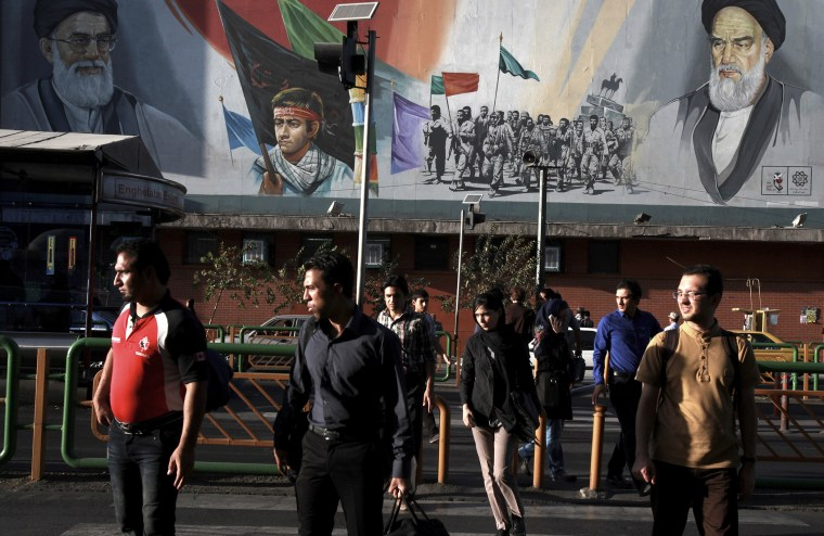 Pedestrians walk past a poster in Tehran depicting Iranian soldiers during the war with Iraq in the 1980s, on Sept. 25, 2013.