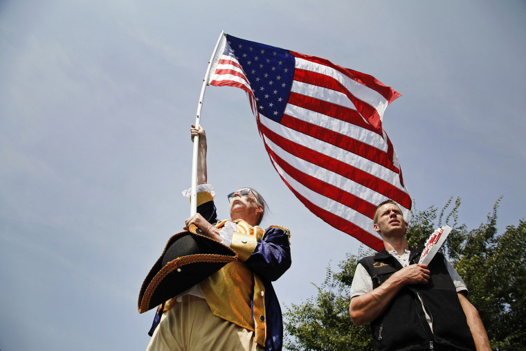 People stand for the national anthem at a Tea Party Patriots rally on the west lawn of the U.S. Capitol, Sept. 10, 2013.