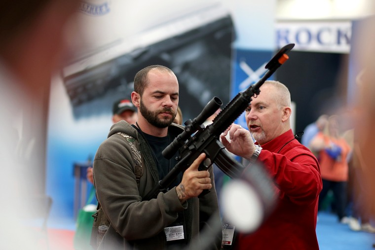 An attendee inspects a scope on an assault rifle during the 2013 NRA Annual Meeting and Exhibits in Houston, Texas, May 3, 2013.