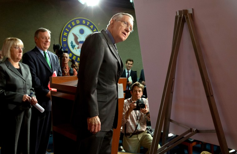 Senate Majority Leader Harry Reid of Nev., right, looks at a placard during a news conference in  Washington, on Nov. 21, 2013