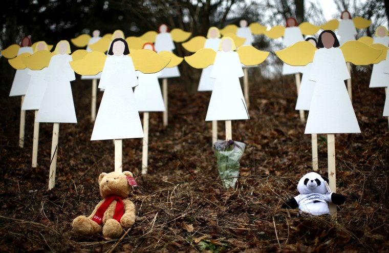 Stuffed animals left by mourners sit beneath some of the 27 wooden angel figures beside a road near the Sandy Hook Elementary School for the victims of a school shooting in Newtown, Connecticut Sunday Dec. 16, 2012.