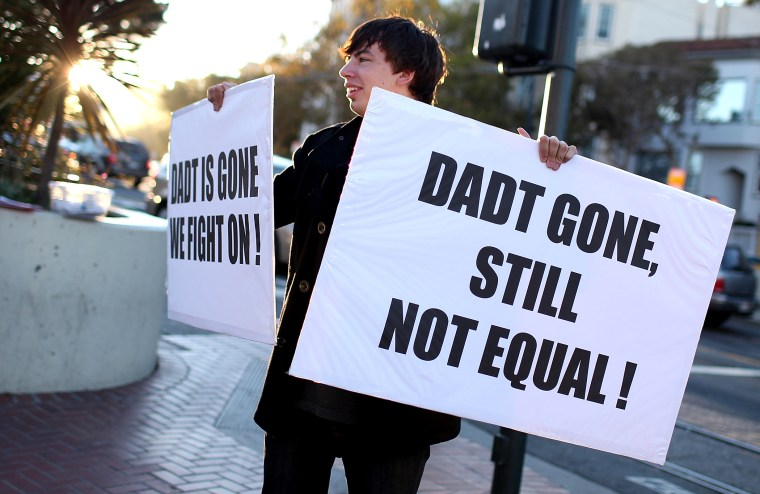 "A protestor holds signs as he celebrates the end of ""Don't Ask, Don't Tell"" but demands equal rights for gays and lesbians on September 20, 2011 in San Francisco, California."