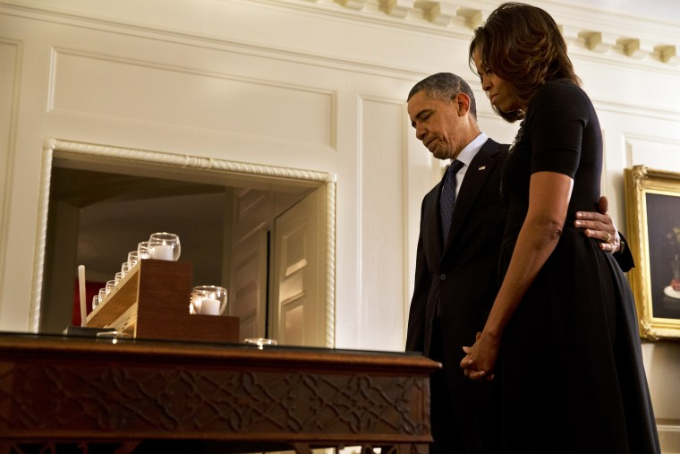 President Barack Obama and first lady Michelle Obama take a moment of silence in honor of the Newtown shooting victims on the one year anniversary of the tragedy, at the White House in Washington, Dec. 14, 2013.