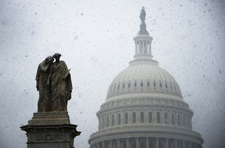 Snow begins to gather on a statue outside the Capitol Building in Washington, DC, Dec. 10, 2013.