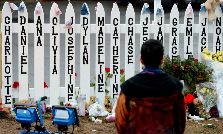On Dec. 21, 2012 a woman kneels in front of a fence with the names of the 20 children killed in the school shooting at Sandy Hook Elementary School in Newtown, Conn.